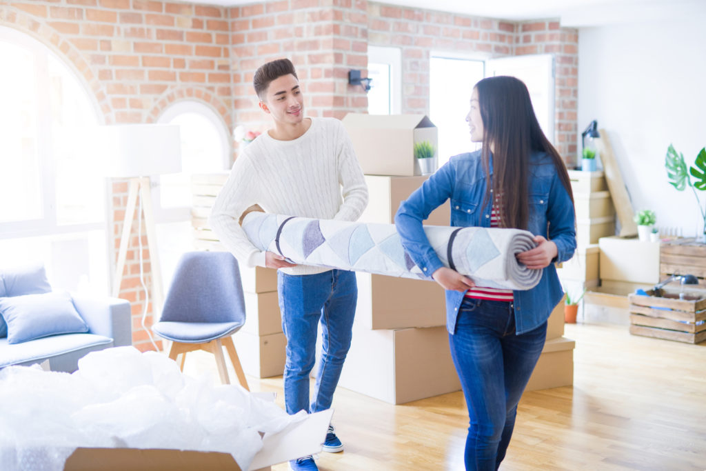 Couple Packing A Rug For Moving